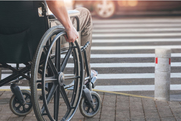 Disabled man on wheelchair preparing to cross the road on pedestrian crossing
